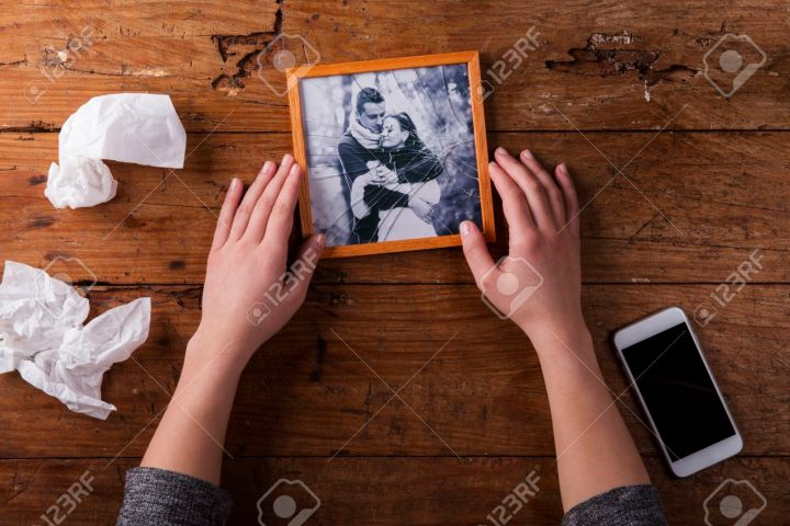 Unrecognizable woman holding broken picture of couple in love. Ended relationship. Crying.Valentines day composition. Studio shot on brown wooden background.