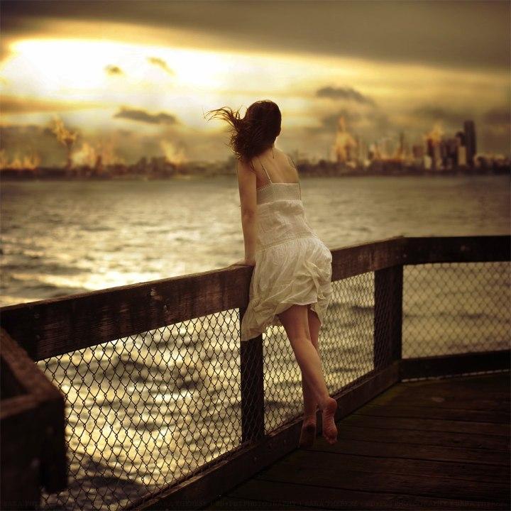 mujer-embarcadero-oceano-atardecer-viento