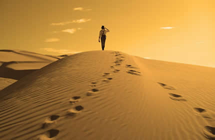 golden-desert-sand-dune-man-back-footprints-walking-sky